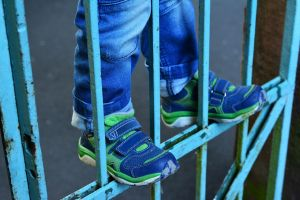 Child climbs on a fence